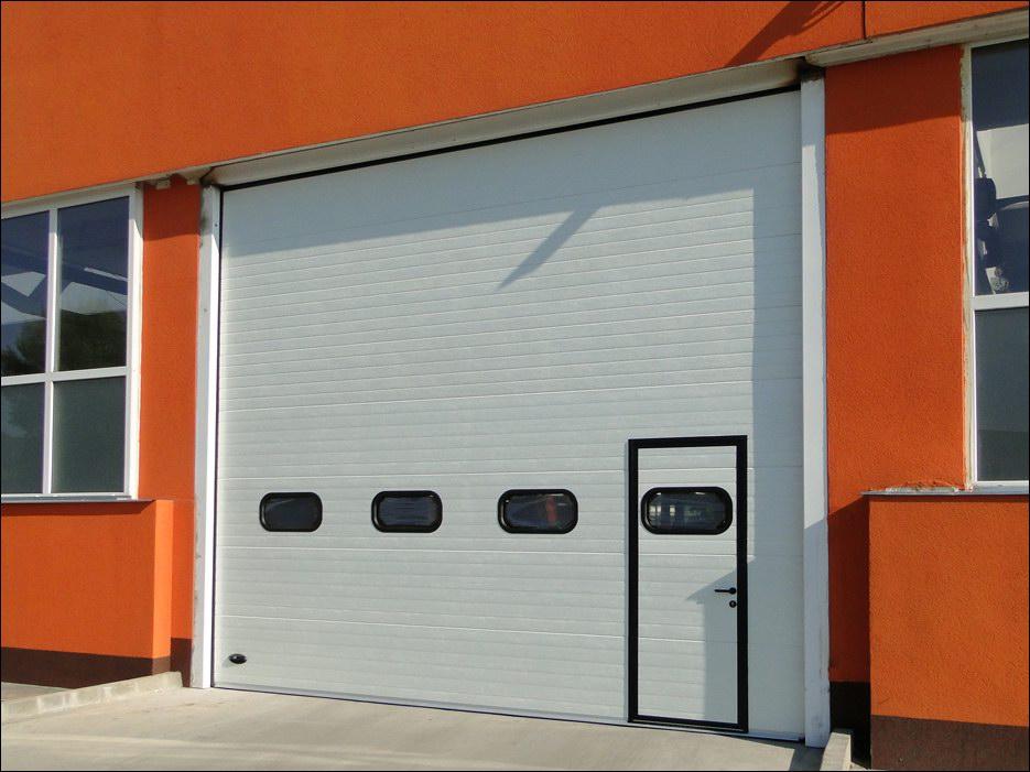 Hőszigetelt, szekcionált ipari kapu, beépített átjáró ajtóval, alacsony küszöbös kivitelben
